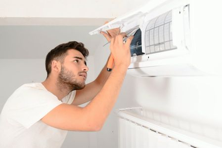 A man cleaning the air ducts in a home.