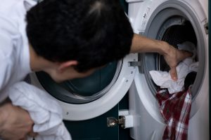 A man reaching into a dryer full of clothes and removing them.